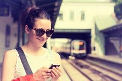 Donna che per mezzo del suo telefono cellulare sul binario del sottopassaggio, controllante programma del treno Fotografia Stock Libera da Diritti