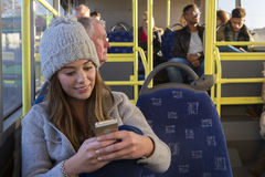 Donna che per mezzo del suo telefono sul bus Fotografia Stock