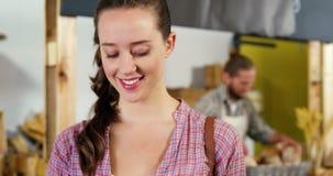 Donna che per mezzo del telefono cellulare alla sezione del forno archivi video