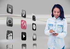 Donna che per mezzo del telefono cellulare con le icone dell'applicazione su fondo grigio Fotografia Stock