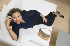Donna che per mezzo del telefono delle cellule sul sofà Immagine Stock