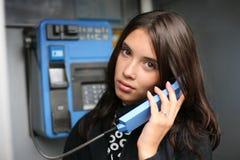 Donna che per mezzo del telefono a gettone fotografia stock