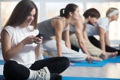 Donna che per mezzo del telefono invece dell'addestramento di sport immagini stock