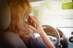 Donna che per mezzo del telefono mentre conducendo l'automobile Fotografie Stock Libere da Diritti