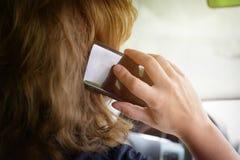 Donna che per mezzo del telefono mentre conducendo l'automobile immagine stock