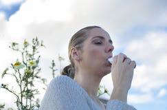 Donna che per mezzo dell'inalatore per trattare asma allergica Fotografie Stock Libere da Diritti