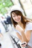 Donna che per mezzo dell'unità handsfree Fotografie Stock