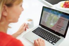 Donna che per mezzo della compressa di Digital per redigere la lista di acquisto a casa Fotografia Stock