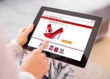 Donna che per mezzo della compressa digitale per comperare online Immagini Stock