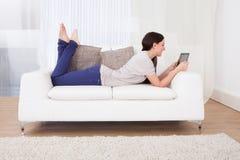 Donna che per mezzo della compressa digitale sul sofà Immagini Stock