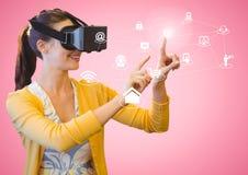 Donna che per mezzo della cuffia avricolare di realtà virtuale con le icone digitalmente generate Fotografia Stock
