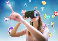 Donna che per mezzo della cuffia avricolare di realtà virtuale con le icone digitalmente generate Immagine Stock