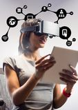 Donna che per mezzo della cuffia avricolare di realtà virtuale e della compressa digitale contro le icone dell'applicazione Fotografia Stock