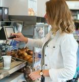Donna che per mezzo della macchina del caffè Fotografie Stock Libere da Diritti