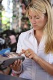 Donna che per mezzo della macchina di debito Fotografia Stock
