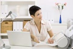 Donna che per mezzo della macchina di fax Fotografia Stock