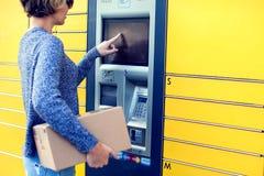Donna che per mezzo della macchina o della serratura automatizzata del terminale della posta di self service fotografie stock