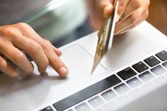 Donna che per mezzo delle mani di credito e del computer portatile card.close-up Fotografie Stock