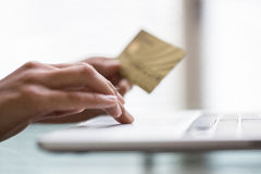 Donna che per mezzo delle mani di credito e del computer portatile card.close-up Immagini Stock