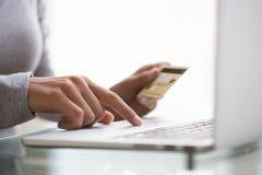 Donna che per mezzo delle mani di credito e del computer portatile card.close-up Fotografie Stock Libere da Diritti