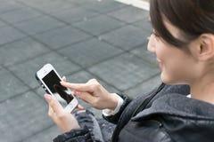 Donna che per mezzo dello smartphone Fotografie Stock Libere da Diritti