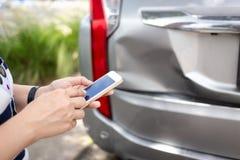 Donna che per mezzo dello smartphone al bordo della strada dopo l'incidente di traffico, traffi immagini stock