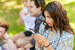 Donna che per mezzo dello smartphone al picnic con gli amici fotografie stock libere da diritti