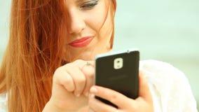 Donna che per mezzo dello smartphone su una spiaggia Fotografia Stock