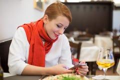 Donna che per mezzo dello smartphone, telefono cellulare in ristorante italiano fotografie stock libere da diritti