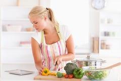 Donna che per mezzo di un calcolatore del ridurre in pani per cucinare Fotografia Stock