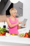 Donna che per mezzo di un calcolatore del ridurre in pani per cucinare Immagini Stock
