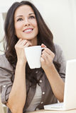 Donna che per mezzo di un calcolatore e bevendo tè o caffè Immagini Stock Libere da Diritti