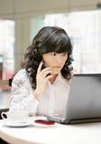 Donna che per mezzo di un cellulare e di un calcolatore Immagine Stock Libera da Diritti