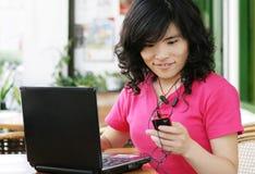 Donna che per mezzo di un cellulare mentre sul calcolatore Immagini Stock Libere da Diritti