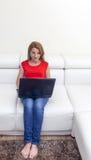 Donna che per mezzo di un computer portatile Immagini Stock