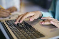 Donna che per mezzo di un computer portatile Immagine Stock