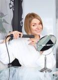 Donna che per mezzo di un raddrizzatore dei capelli Fotografia Stock Libera da Diritti