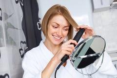 Donna che per mezzo di un raddrizzatore dei capelli Fotografia Stock