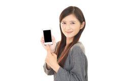 Donna che per mezzo di un telefono astuto Fotografia Stock