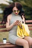 Donna che per mezzo di un telefono astuto Ragazza che manda un sms sullo Smart Phone nella via che porta un rivestimento giallo A Immagine Stock