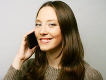 Donna che per mezzo di un telefono cellulare isolato su un fondo bianco Immagini Stock Libere da Diritti