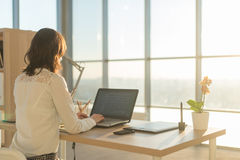 Donna che per mezzo mani di s del computer portatile a casa 'sul computer portatile Immagini Stock