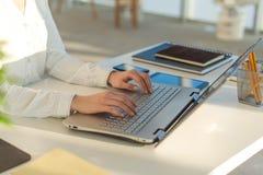 Donna che per mezzo mani di s del computer portatile a casa 'sul computer portatile Immagini Stock Libere da Diritti