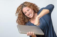 Donna che perfora il suo computer portatile Immagini Stock Libere da Diritti