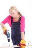 Donna che perfora un pozzo in una plancia di legno Fotografie Stock