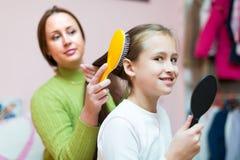 Donna che pettina i capelli della ragazza Fotografia Stock Libera da Diritti