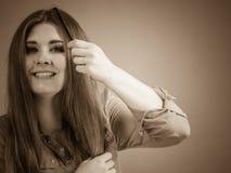Donna che pettina i suoi capelli marroni Fotografia Stock