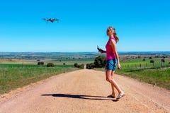 Donna che pilota un fuco nel paesaggio rurale fotografie stock libere da diritti