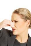Donna che pizzica naso a causa dell'odore fotografia stock