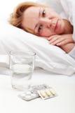 Donna che pone malato con le pillole ed il bicchiere d'acqua Fotografie Stock Libere da Diritti